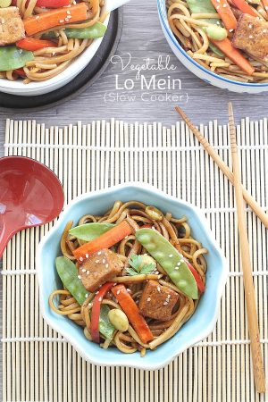 A small blue serving bowl with a delicious Slow Cooker Vegetable Lo Mein with beautiful wooden chopsticks.