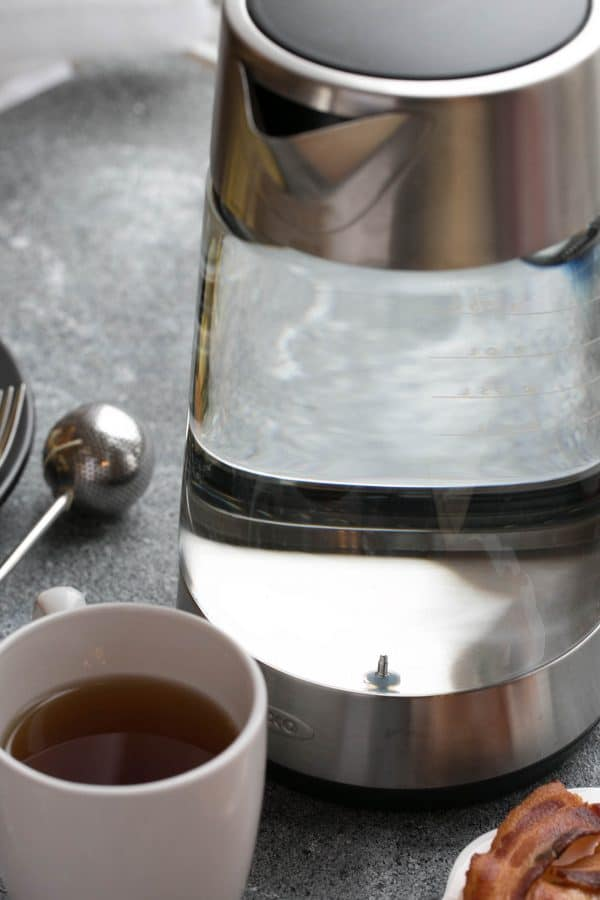 Oxo kettle with water in front of a cup of tea