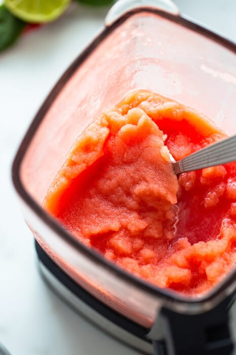 The Combined Frozen Drink Ingredients in a Blender with a Metal Spoon