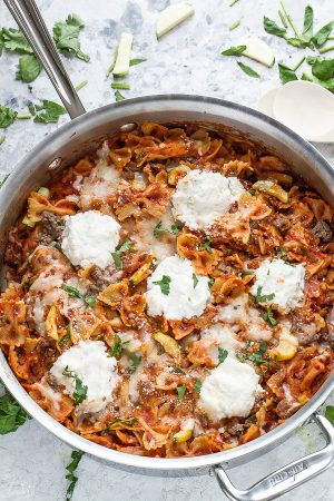One pot Easy Skinny Skillet Lasagna in a large silver skillet surrounded by parsley and cheese on a table.