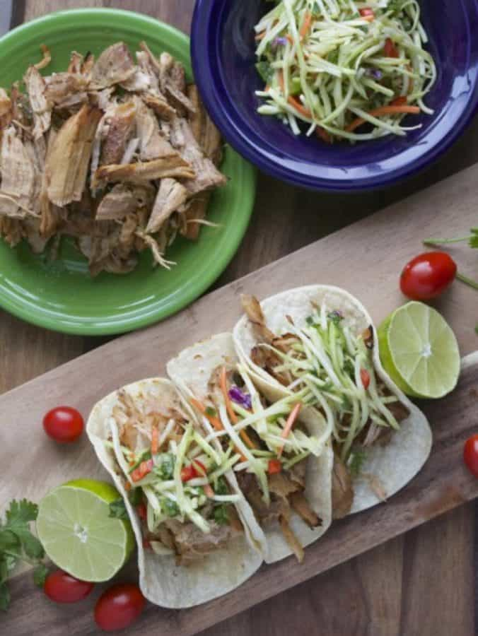 Overhead view of Jalapeno Ranch Carnitas tacos on a platter with a bowl of shredded carnitas and broccoli slaw