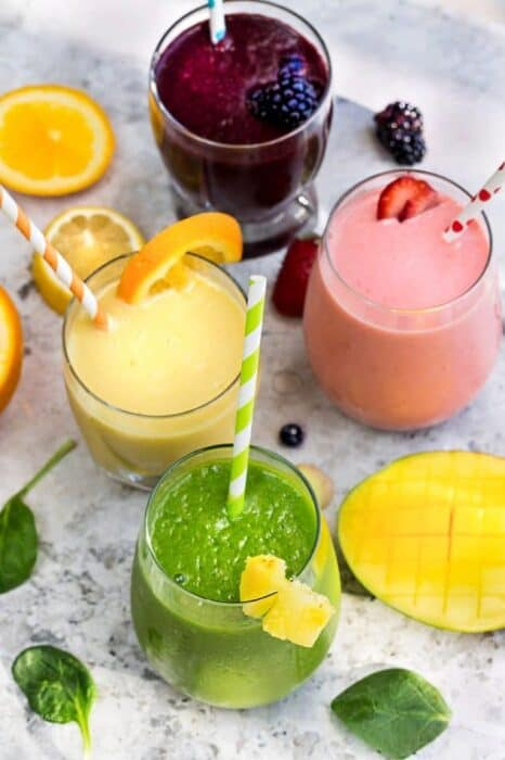 Top view of five healthy smoothie recipes in a clear glass with a straw on a grey marble background with fruit
