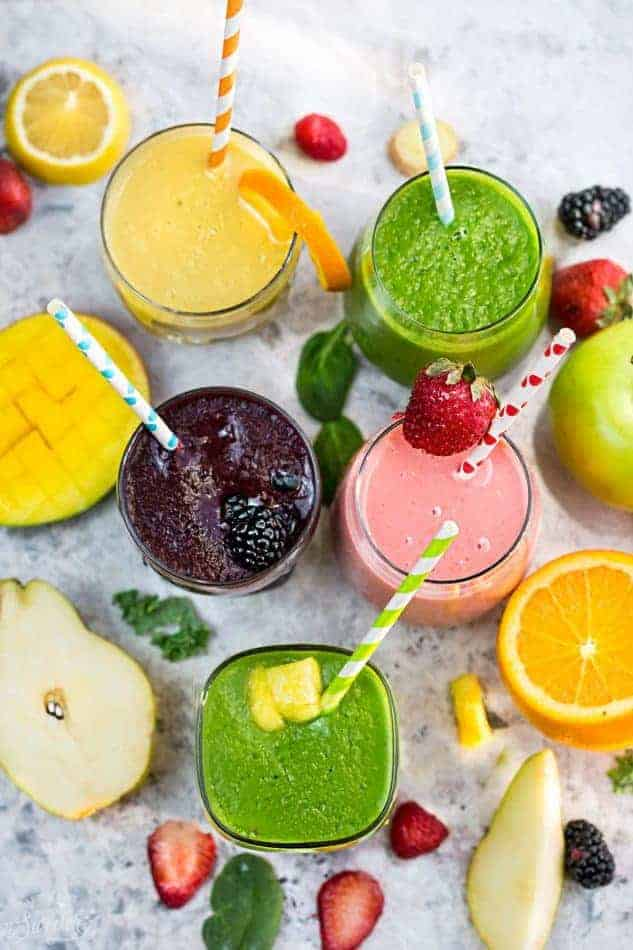 Top view of five healthy smoothies in a clear glass with a straw on a grey marble background with fruit