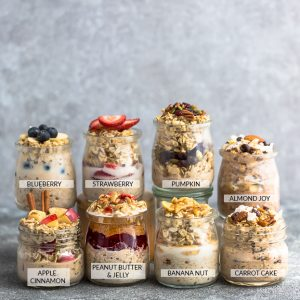 Side view of 8 jars of overnight oats with flavor labels on a grey background. Flavors include: Almond Joy, Apple Cinnamon, Banana Nut, Blueberry, Carrot Cake, Peanut Butter & Jelly, Pumpkin Cranberry and Strawberry.