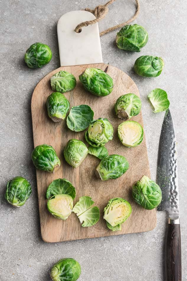 Top view of trimmed Brussels sprouts on a wooden cutting board with a knife