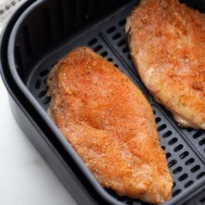 Top view of seasoned chicken breast in the air fryer