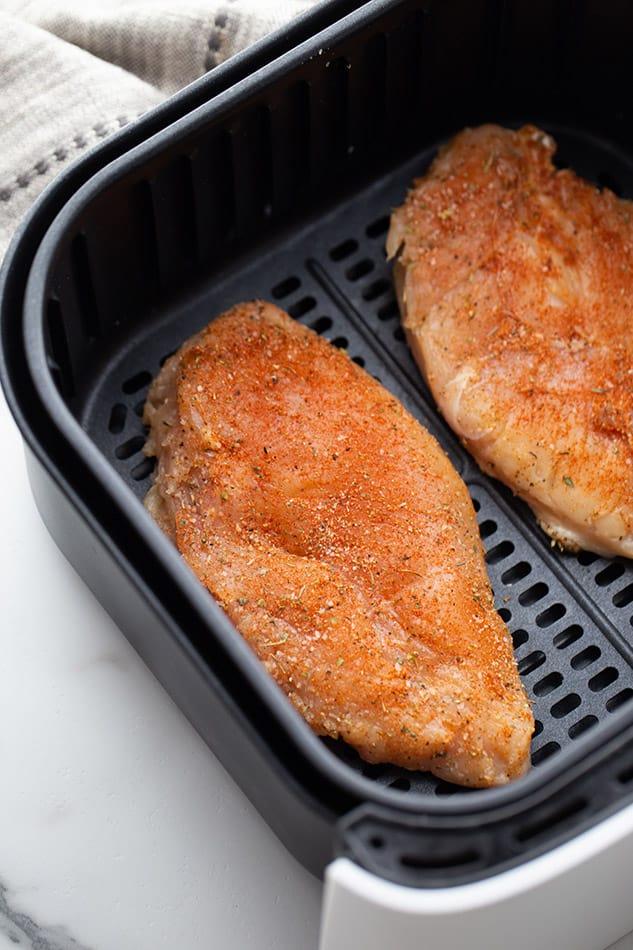 Top view of seasoned chicken breast in the air fryer