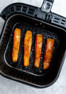 Top view of four air fried salmon in the air fryer basket