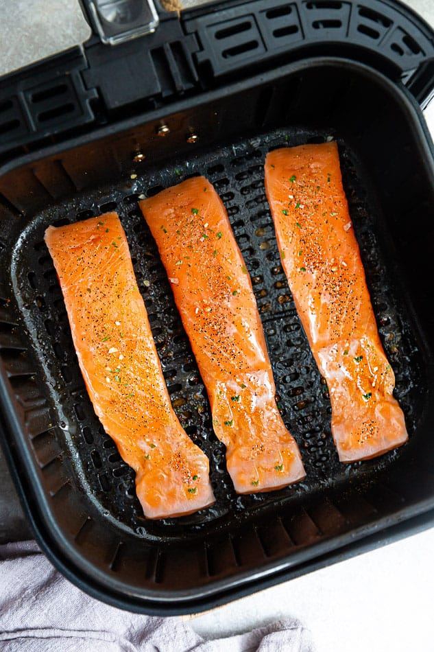 Top view of three raw salmon fillets in the air fryer basket