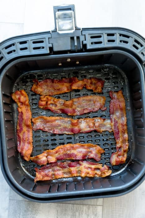 Top view of air fried bacon in an air fryer basket