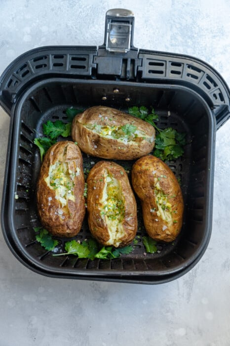 Overhead view of 4 baked potatoes cut open with fresh herbs in an air fryer