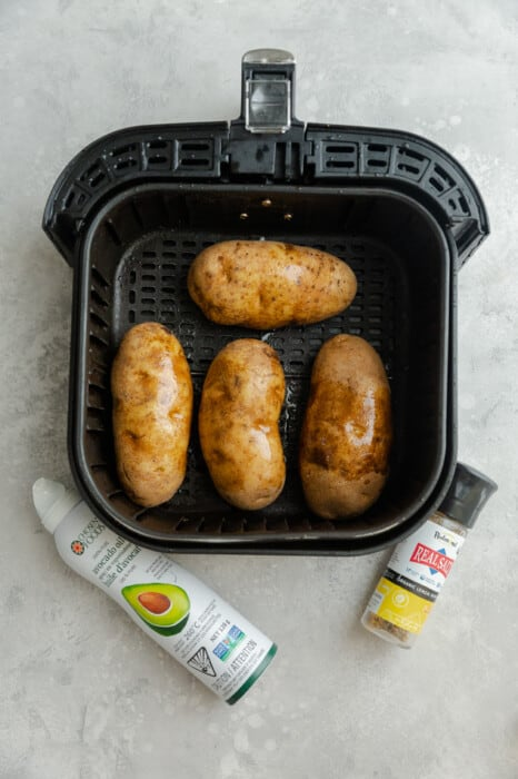 Overhead view of 4 potatoes in an air fryer next to cooking spray and salt