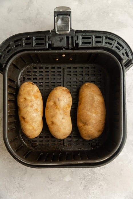 Overhead view of 3 potatoes in an air fryer