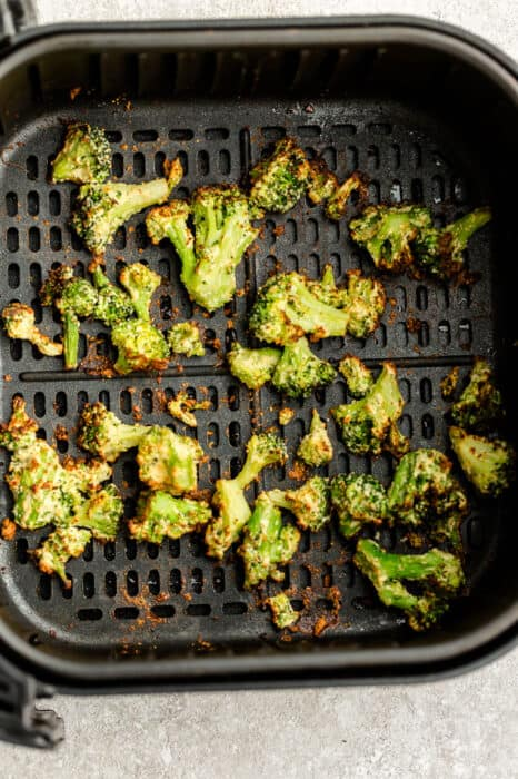 Top view of air fried broccoli in the air fryer basket