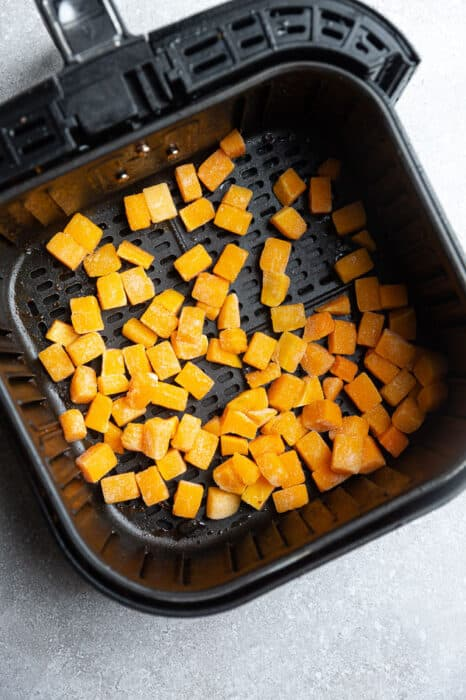 Top view of frozen butternut squash cubes in an air fryer basket