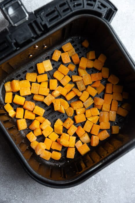 Top view of chopped raw butternut squash cubes in an air fryer basket