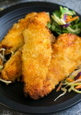 Close-up view of Air Fryer Chicken tenders on a black plate with coleslaw