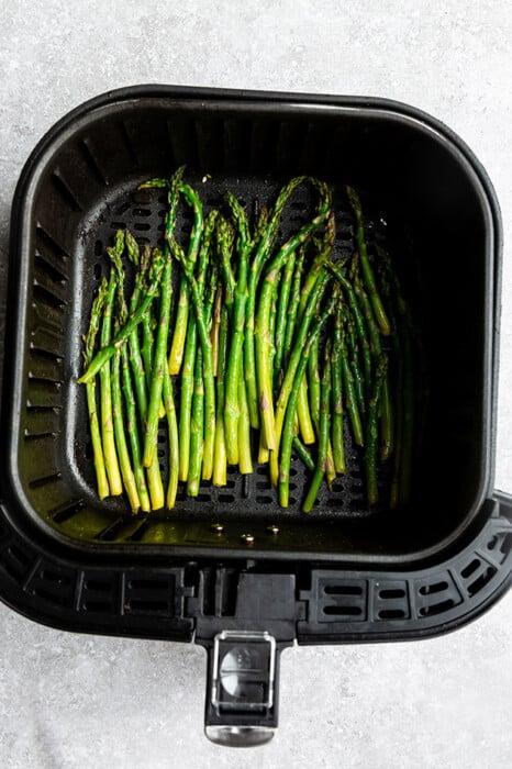 Top view of air fried asparagus in an air fryer basket
