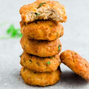 Side view of 5 stacked crispy salmon cakes one with a bite on a white background