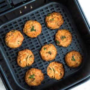 Top view of crispy air fryer salmon patties in black air fryer basket.
