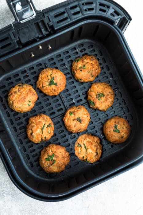 Top view of crispy air fryer salmon patties in black air fryer basket.