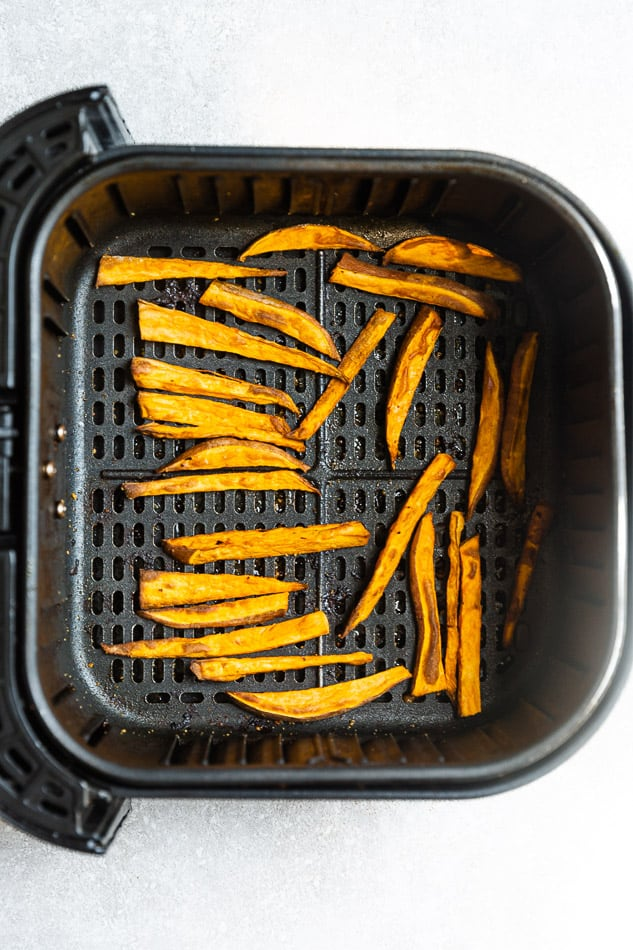 Image of cooked sweet potato fries in black air fryer basket.
