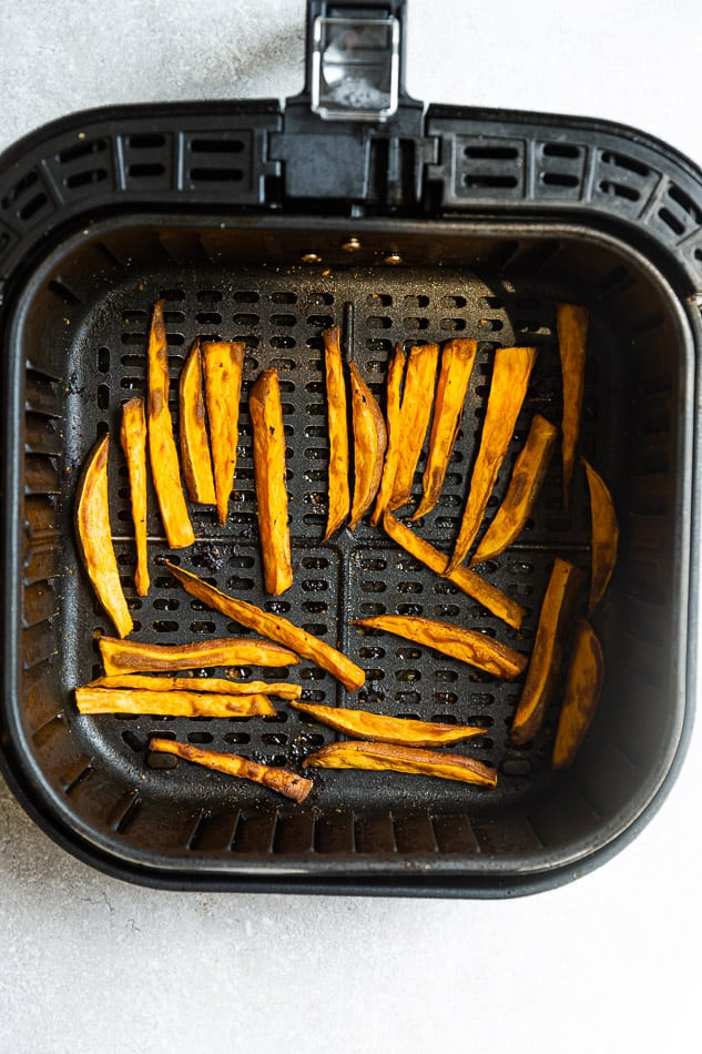 Overhead image of sweet potato fries in air fryer basket.