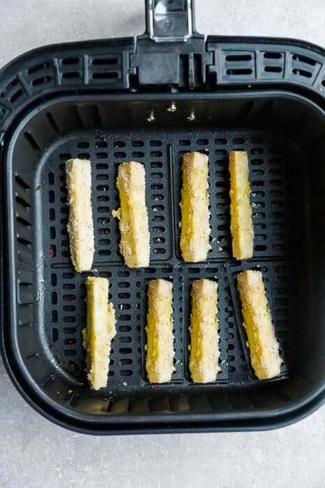 Top view of 8 air fryer zucchini fries in an air fryer basket