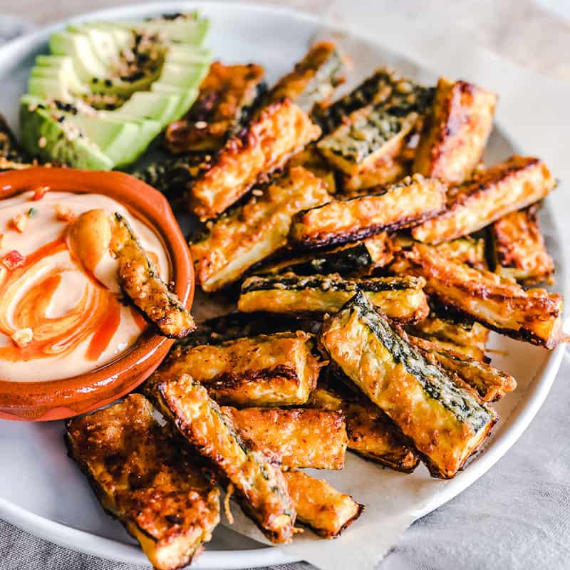 Side view of crispy baked zucchini fries on a white bowl with a bowl of dip and avocado slices