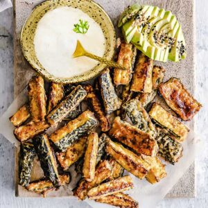 Top view of air fryer zucchini fries on a wooden cutting board and parchment paper with dip and avocado