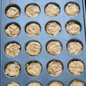 Top view of apple donut hole batter in a mini 24 count muffin pan