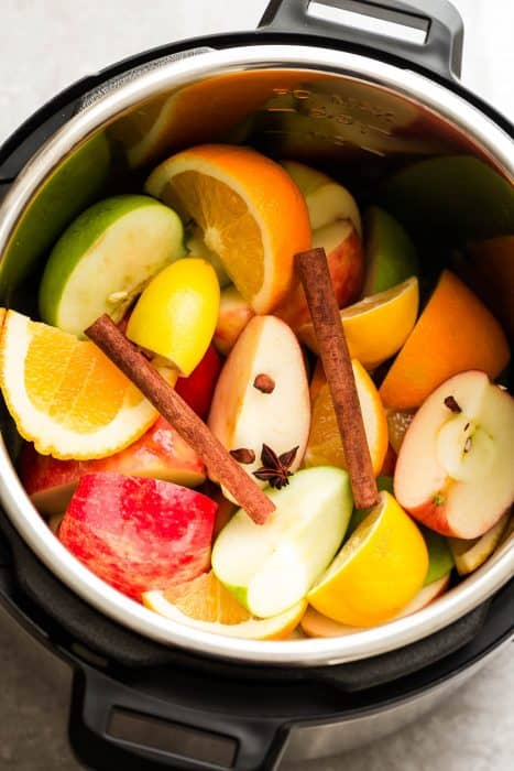 Top view of apples, oranges, cinnamon and cloves in an Instant Pot pressure cooker