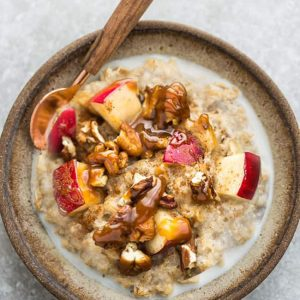 A bowl of apple oatmeal with a spoon topped with chopped apples, pecans, almond butter.