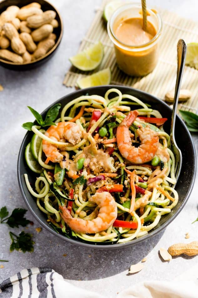 A serving of Asian Zucchini Noodle Salad with Thai Peanut Dressing topped with shrimp in a bowl