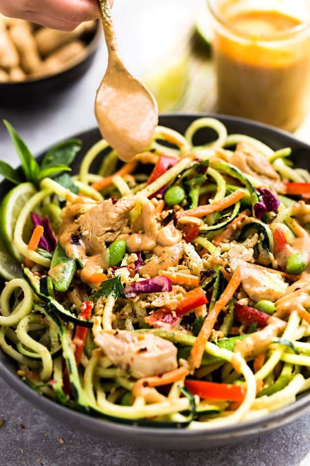 Thai Peanut Dressing being drizzled over Asian Zucchini Noodle Salad