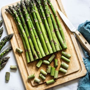 Top view of uncooked asparagus spears on a wooden cutting board with a knife