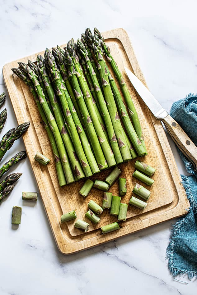 Asparagus on wooden cutting board with knife and blue towel.