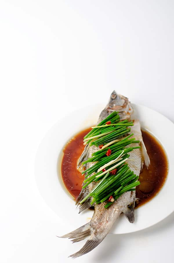 Whole Chinese Steamed Fish covered with chives on a plate with soy sauce