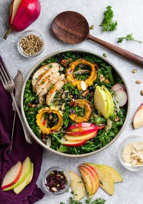 Top view of Autumn Harvest Salad with apple, pear and chicken in a bowl with forks