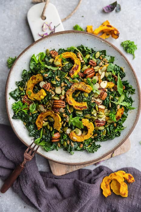 Top view of Fall Salad with Kale & roasted delicata squash in a bowl with a copper fork
