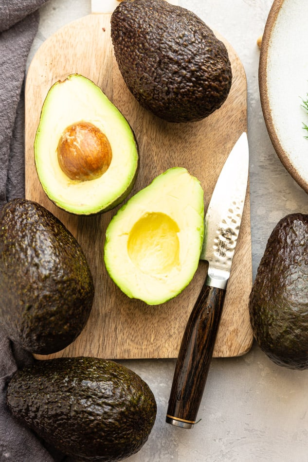 Top view of two halved avocados on a wooden cutting board with a knife