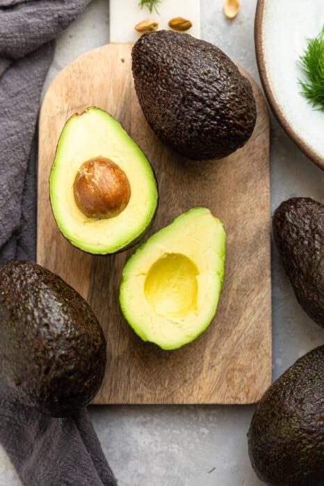 Top view of two halved avocados on a wooden cutting board