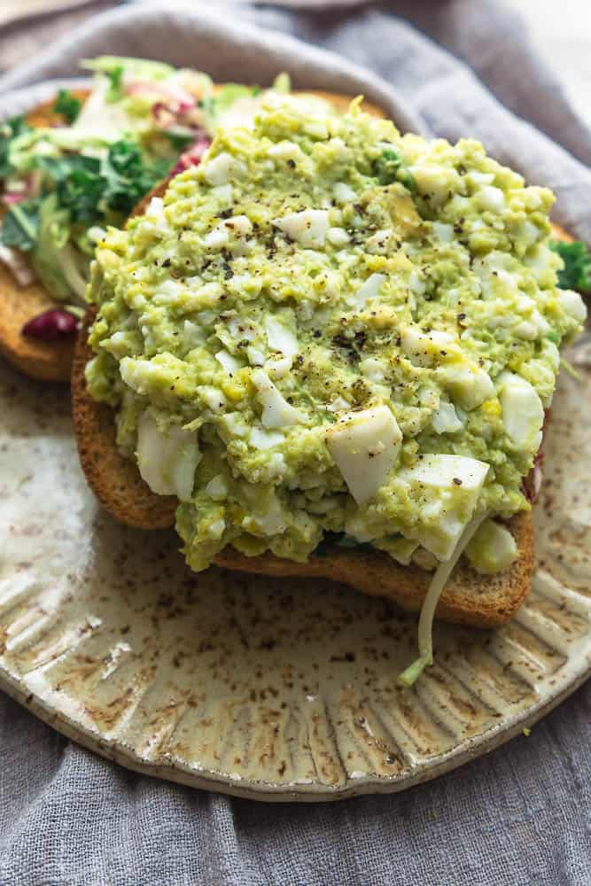 Top close up view of paleo avocado egg salad on a piece of low carb bread