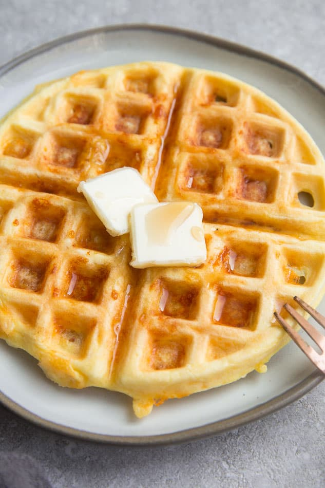 Side view of chaffles on a white plate with butter and sugar free syrup with a fork
