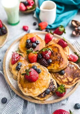 Top view of six keto coconut flour pancakes on a plate with strawberries, blueberries and sugar free syrup on a grey background