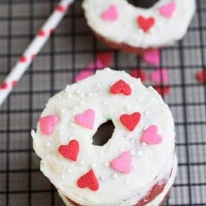 Baked Red Velvet Cake Donuts with Cream Cheese Glaze and heart shaped sprinkles on a cooling rack