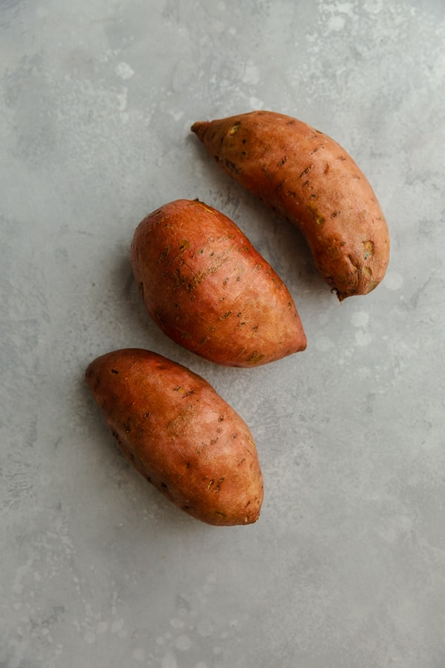 3 raw sweet potatoes on a gray background