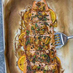 Six Baked Salmon Fillets on a Pan with Orange Slices Slid Halfway Underneath Them