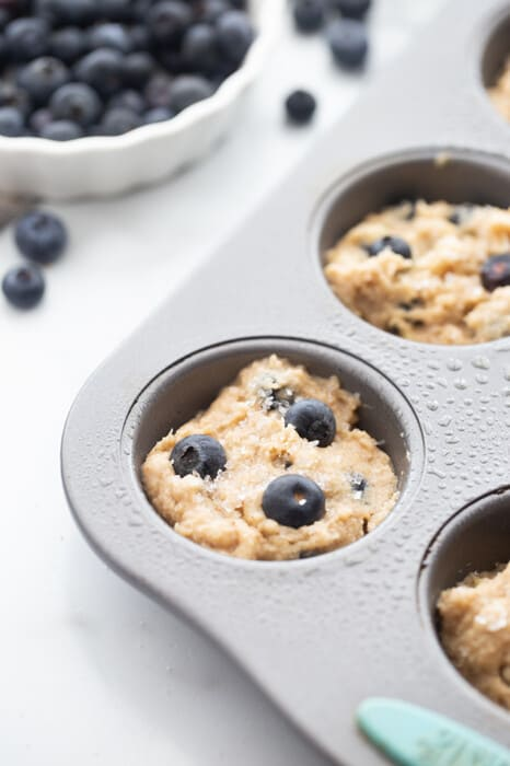 Close-up view of blueberry muffin batter in muffin pan