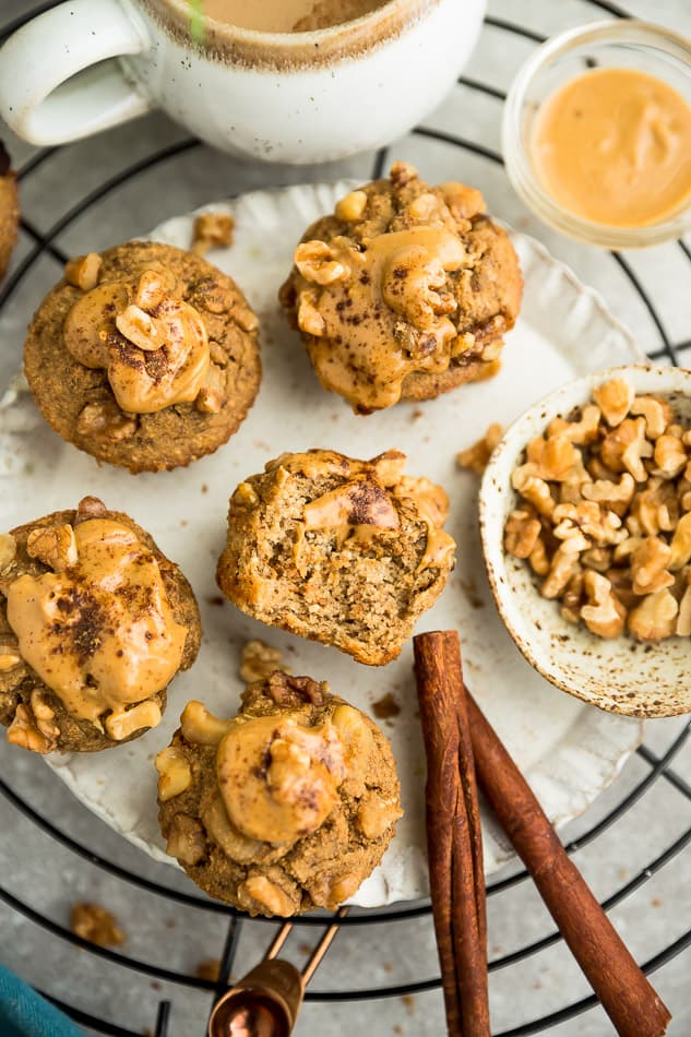 Top view of keto muffins with almond butter and walnuts on white plate.